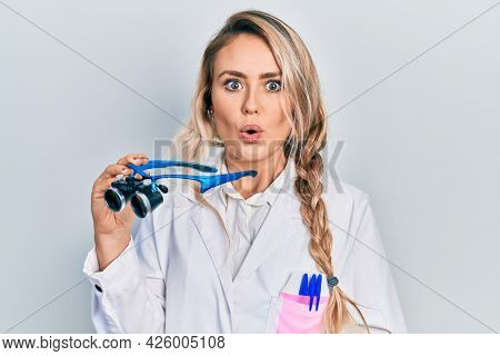 Beautiful young blonde woman holding scientist glasses scared and amazed with open mouth for surprise, disbelief face