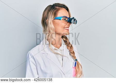 Beautiful young blonde woman wearing optometry glasses looking to side, relax profile pose with natural face and confident smile.