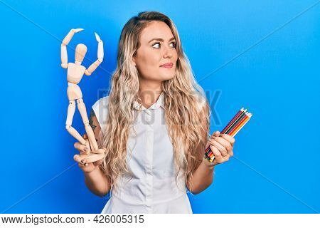 Beautiful young blonde woman holding wooden manikin and colored pencils smiling looking to the side and staring away thinking.