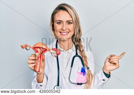 Beautiful young blonde woman holding anatomical model of female genital organ smiling happy pointing with hand and finger to the side