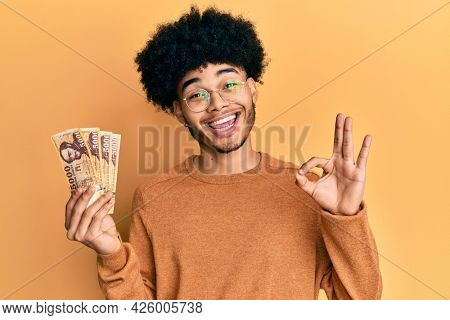 Young african american man with afro hair holding 5000 hungarian forint banknotes doing ok sign with fingers, smiling friendly gesturing excellent symbol