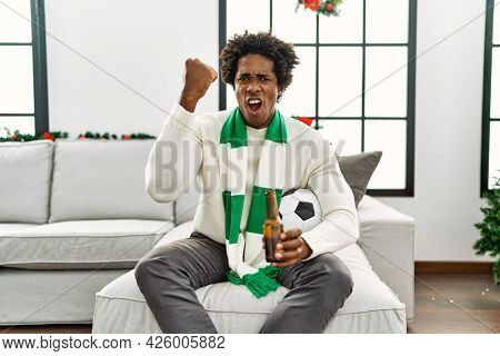 Young african american man football hooligan drinking beer cheering game annoyed and frustrated shouting with anger, yelling crazy with anger and hand raised