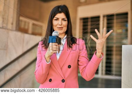 Middle age reporter woman holding microphone doing television speech outdoors