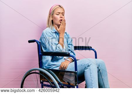 Beautiful blonde woman sitting on wheelchair bored yawning tired covering mouth with hand. restless and sleepiness.