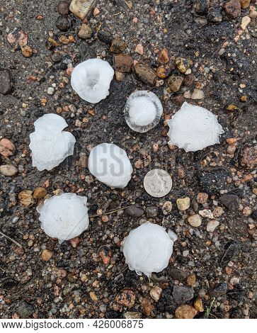 Several Large Hail Stones From A Severe Thunderstorm Laying On Asphalt With A U.s. Quarter To Provid