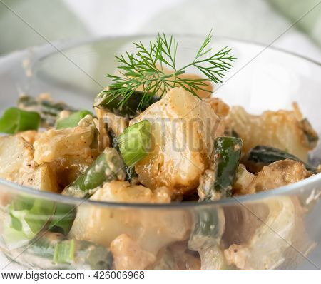 Close Up View Of A Bowl Of Creamy Potato And Bean Salad Garnished With Dill, Ready For Eating.