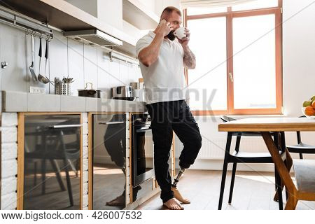 White man with prosthesis talking on cellphone while drinking coffee at home