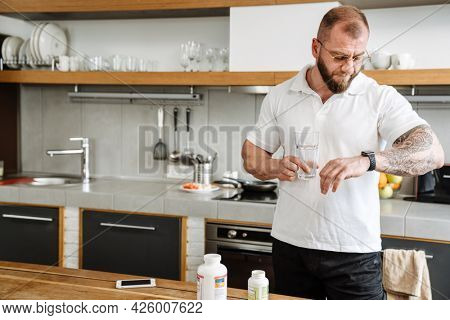 White man in eyeglasses looking at wristwatch while taking her medicine in kitchen