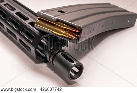 The Barrel And Muzzle Of A 223 Caliber Ar 15 Rifle With A Loaded Magazine For It Next To It With A W