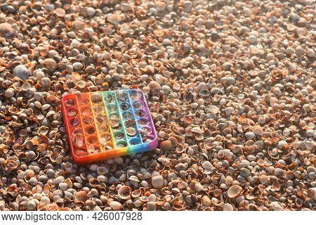 Seashells With An Anti-stress Toy. Rainbow Pop It Toy On Seashells.
