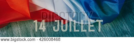 the text 14 juillet, 14 july, the national day of france written in french, and a french flag on a gray rustic wooden background, in a panoramic format to use as web banner or header