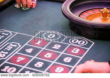 Minsk. Belarus - 25.06.2021 - Chips On A Casino Playing Table. Green Table Cover.