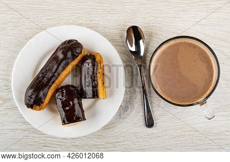 Whole Eclair With Chocolate Glaze, Halves Of Eclair In White Plate, Teaspoon, Cup Of Cocoa With Milk