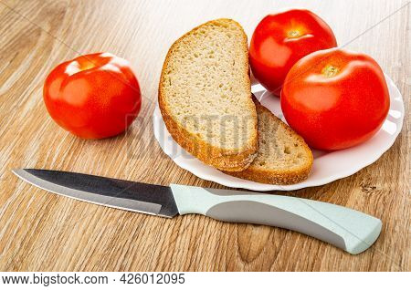 One Tomato, Kitchen Knife On Wooden Table, Red Tomatoes, Slices Of Bread In White Plate On Wooden Ta