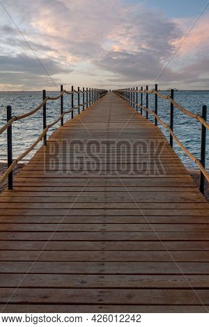 Wooden Pier Extending Into The Sea For Tourists At Sunrise.