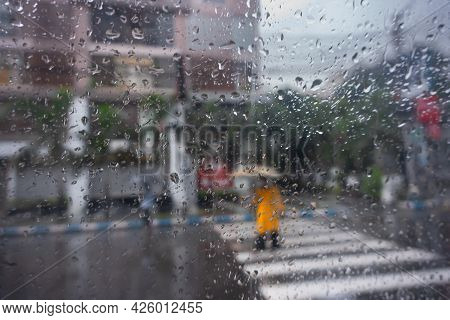 Image Shot Through Raindrops Falling On Wet Glass, Abstract Blur Of City Road Zebra Crossing - Monso
