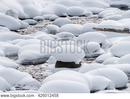 winter shot of soda butte creek and rocks covered in snow at yellowstone national park
