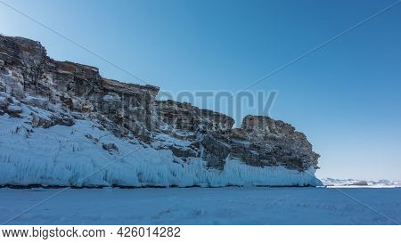 A Granite Rocky Island Devoid Of Vegetation Rises Above A Frozen Lake. Cracks In Stones, Icicles On