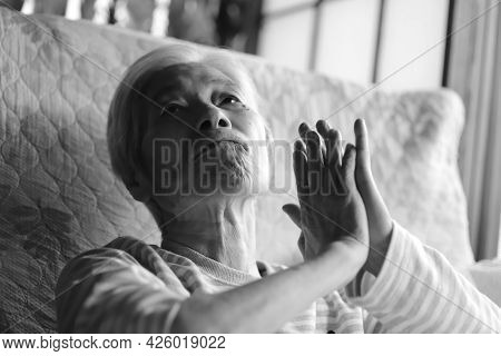 An Elderly Woman With Dementia Looking Up With Her Hands Together While Relaxing In A Nursing Bed