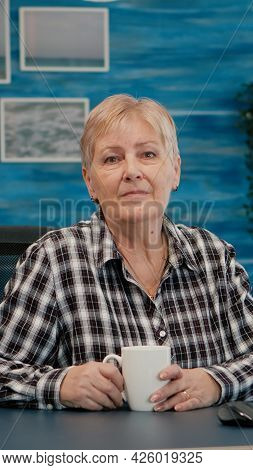 Senior Focused Woman Looking At Camera Sitting In Workplace At Desk Working From Home While Old Husb
