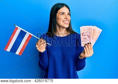 Young hispanic woman holding thailand flag and baht banknotes smiling looking to the side and staring away thinking.