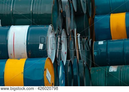 Old Chemical Barrels Stack. Blue, Green, And Yellow Chemical Drum. Steel Tank Of Flammable Liquid. H