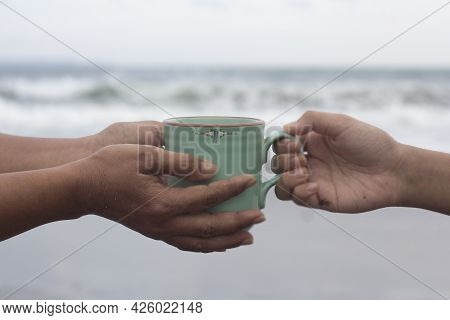 Hands Of Two People Holding A Cup Of Coffee Or Tea On Beach Background. Take And Give Or Giving And