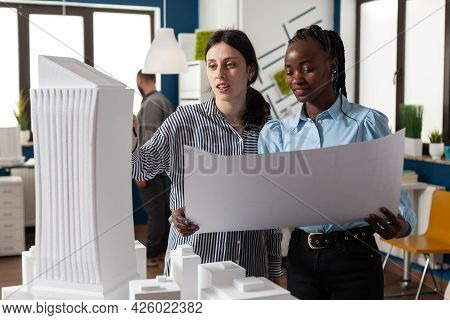 Colleagues Architects Women Checking Plans Of Blueprints Layout Design. Multi Ethnic Team Of Profess
