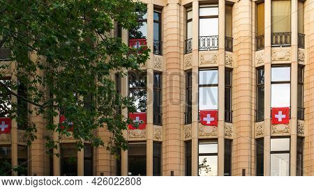 Flags Of Switzerland Hang On From Balcony In Lausanne, Switzerland. Swiss Flags.