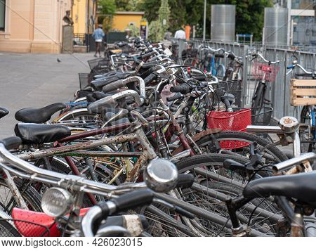Many Old Bicycles Padlocked To The Rack Near Train Station.