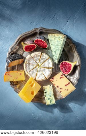 Cheese Platter With Brie, Blue Cheeses, Fruits, Swiss Cheese And Others, Shot From Above On A Blue B
