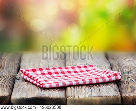 Red Picnic Table Cloth Napkin On Wooden Plank Table Blur Nature Background.retro Design Empty Space