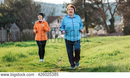 Happy Caucasian Grandmother And Granddaughter Running Together. Old And Young Women In Sports Clothe