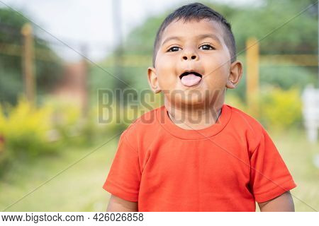 Portrait Of Cute Little Indian Toddler Grimacing By Making Tongue Out While Playing At Park With Cop