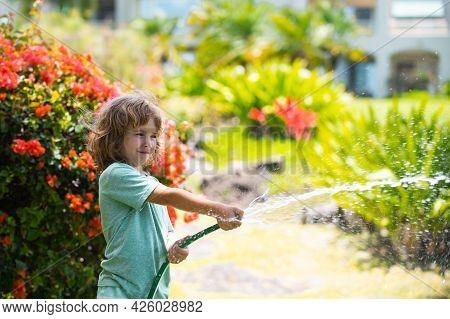 Cute Little Boy Watering Flowers In The Garden At Summer Day. Child Using Garden Hose. Funny Kid Wat