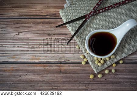 Tasty Soy Sauce In White Ceramic Bowl Scoop And Organic Soybean With Chopsticks And Apron On Wood Ta