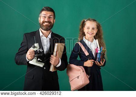 School Girl With Funny Amazed Teacher In School. Studio Portrait Of Tutor And Young School Girl With