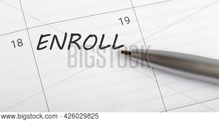 Text Enroll On Calendar Planner To Remind You An Important Appointment With A Pen On The Isolated Wh