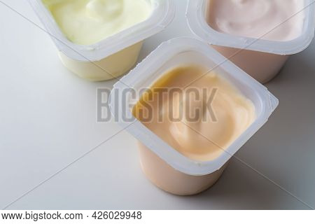 Flavoured Yogurt In Plastic Pots - Colourful Fruit Flavoured Yogurt Cups Isolated On White With Copy