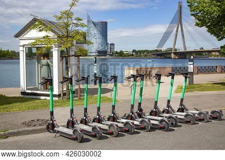 Latvia, Riga, May, 2021 - Electric Scooters Lined Up On A Sidewalk Waiting To Be Rented On The Emban