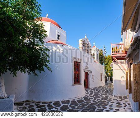 Traditional Greek Orthodox Church In Greek Island Town. Red Dome, Whitewashed Walls, Greek Flag And