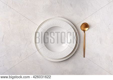 Empty White Plate And Golden Spoon. Kitchen Utensils Set On Light Gray Table. Top View Flat Lay With