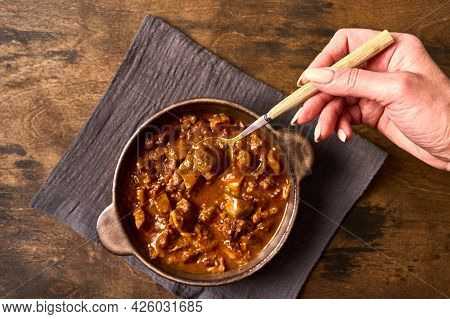 Womans Hand Holds A Fork With Traditional Goulash Meat In Ceramic Bowl On Napkin. Top View
