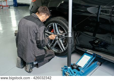 Mechanic Changing Car Wheel In Auto Repair Shop Using Lift Jack And Electric Drill To Loosen The Bol