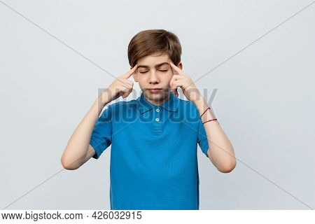 Serious Boy 12-14 Years Old Wearing Casual Blue T Shirt Pointing To Head With Two Fingers And Deeply