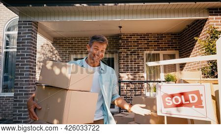 Cheerful Man Holding Boxes And Pointing With Hand At Sold Board Near New House.