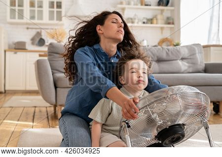 Relaxed Mom And Little Kid Sit With Closed Eyes At Fan In Living Room Refreshing From Summer Heat Ou