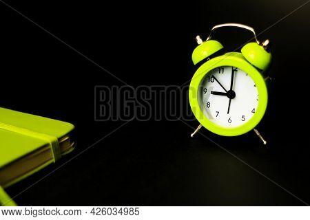 Alarm Clock Morning Wake-up Time. Light Green Alarm Clock On A Black Background. Time Minimalistic C