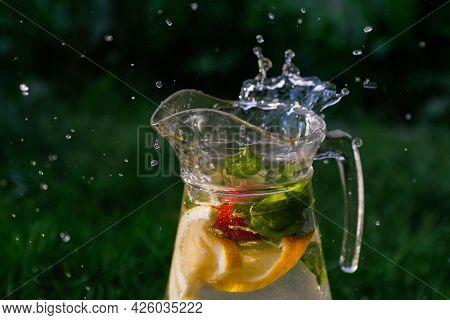 Defocus Splash Water Bubbles In Glass Jug Of Lemonade With Slice Lemon And Mint On Natural Green Bac