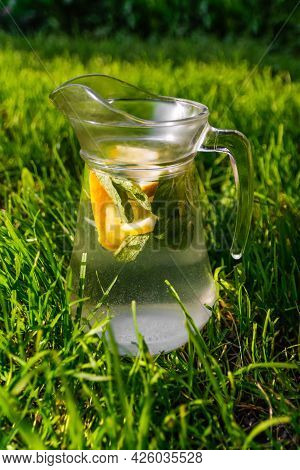 Defocus Glass Jug Of Lemonade With Slice Lemon And Leaves Of Mint On Natural Green Background. Pitch
